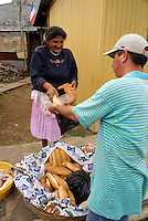 Elderly woman buying fresh loaves of bread in the village of Ataco in western El Salvador