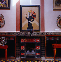 An Art Deco print hangs above a red and black tiled fireplace which is flanked by console tables and Venetian mirrors