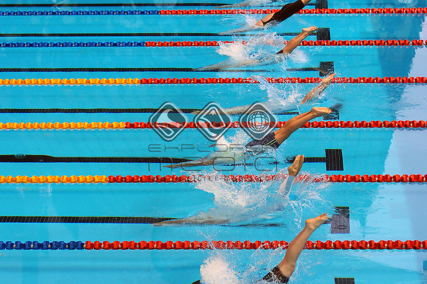 Swimmers dive into the water at the start of a race.