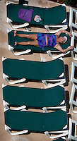 A woman lounges on chairs at poolside at a hotel near the ocean in Virginia, Beach, VA.