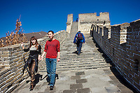 Tourist couple walk the ancient Great Wall of China at Mutianyu, north of Beijing, China