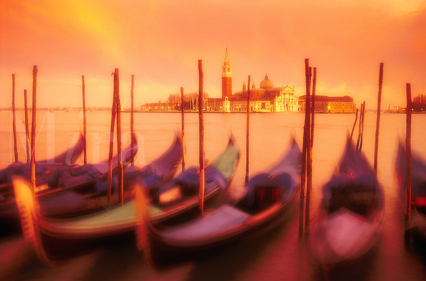 Italy,Venice. Gondolas moored at Molo San Marco at dusk. Gondolas blurred with time exposure