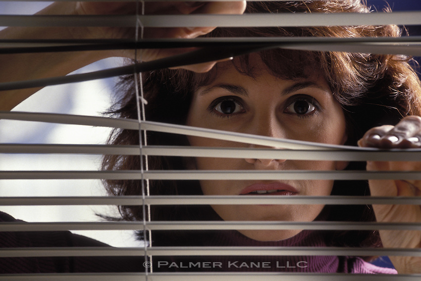 Woman parting venetian blinds to look out at something
