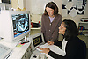 Registrar of radiology examining patient's CT Scan and making observational notes,