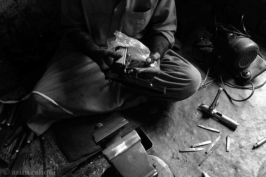 a worker checks a hand gun after final assembly and testing.  darra adam khel, tribal areas, pakistan.  september 2003&amp;#xA;&amp;#xA;copyright asim rafiqui 2003<br />