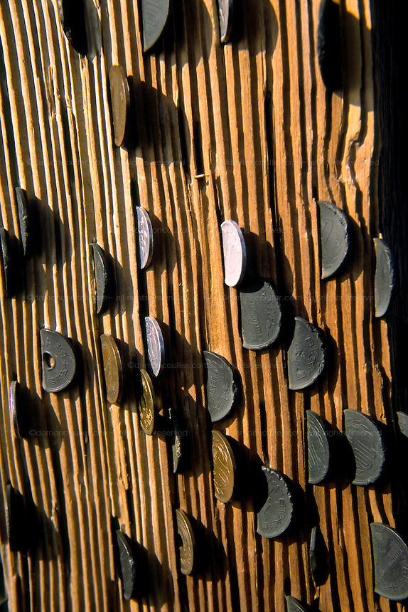 Coins knocked into the woodwork of a Torii gate on the summit of Mount Fuji, at 3,776 metres, the highest peak in Japan. Yamanashi Prefecture, Japan August 2005