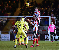 Lincoln City's Scott Wharton gets above Lincoln City's Michael Bostwick and Cheltenham Town's Elijah Adebayo and Kevin Dawson to head clear<br /> <br /> Photographer Andrew Vaughan/CameraSport<br /> <br /> The EFL Sky Bet League Two - Cambridge United v Lincoln City - Friday 9th February 2018 - Abbey Stadium - Cambridge<br /> <br /> World Copyright &copy; 2018 CameraSport. All rights reserved. 43 Linden Ave. Countesthorpe. Leicester. England. LE8 5PG - Tel: +44 (0) 116 277 4147 - admin@camerasport.com - www.camerasport.com