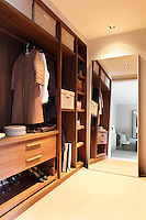 A full length mirror reflects the built-in storage of this dressing room, which houses specialised areas for storing shoes, hanging clothes, and shelves for boxes