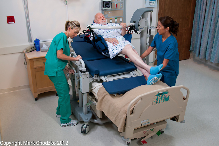 Nurses lift patient from bed using KCI lifting device