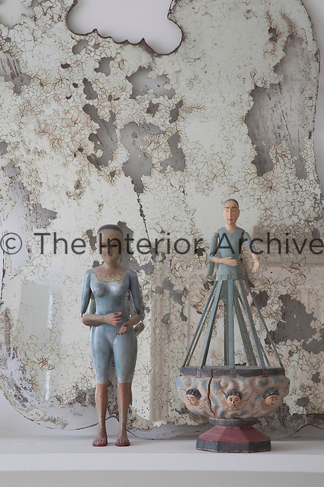 Two antique dolls, thier original clothes long gone, stand against an old tarnished mirror, its metal backing flaked away leaving mostly glass front