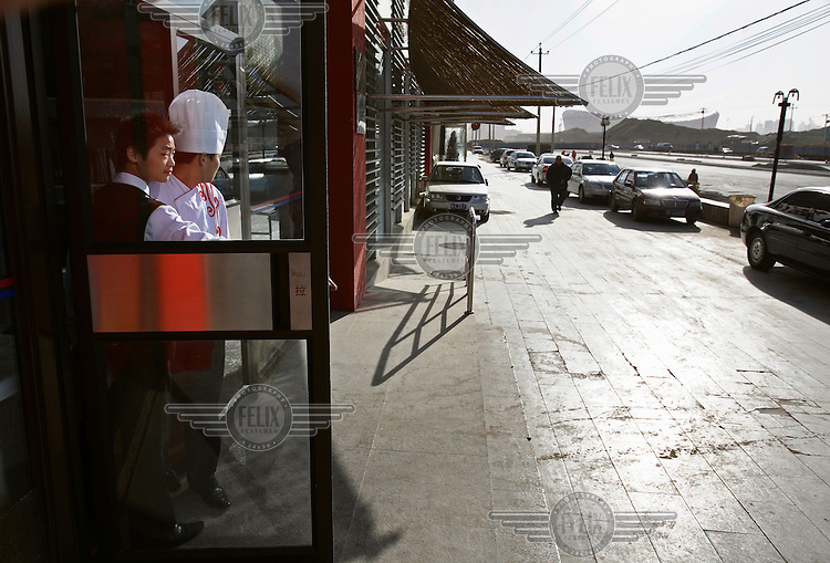 """The """"Bird's Nest"""" stadium can be seen to the right as a waiter and cook look out of their restaurant, which is close to the 2008 Olympic Games venue..."""