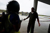 A member of a Foreign Office Rapid Deployment Team talks to airport staff during a humanitarian needs assessment mission to Dominica. The Caribbean island of Dominica was devasted  by the category 5 Hurricane Maria on Sept 19th, and the Prime Minister of the country, Roosevelt Skerrit requested emergency international asssitance. The UK already had military aircraft in the region responding to the damaged caused by Hurricane Irma. A Chinook helicopter from 27 Squadron RAF was tasked to take a needs assessment team to the island, made up of expert Royal Engineers, humanitarian experts from DFID and the UN, and members of the Caribbean Disasters & Emergencies Management Agency. The team was the first international assistance to arrive on the island at Douglas Charles airport, which was cut-off by the storm.