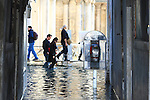Tourist walk on flooded St Mark's square during an acqua alta (high-water). The Acqua Alta, a convergence of high tides and a strong sirocco, reached 125 centimetres in Venice, on November 20, 2013.  <br /> <br /> &copy; Pierre Teyssot