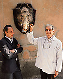 ITALY, Orvieto, Umbria, Chef Alex Palermo standing with Butcher Emilio Batalocco beside a boar's head on the wall.