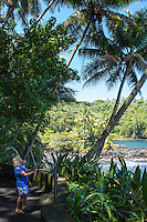 A tourist with a selfie stick takes photos along the coastline at Hawaii Tropical Botanical Garden, Hamakua coastline, Big Island of Hawaiʻi.