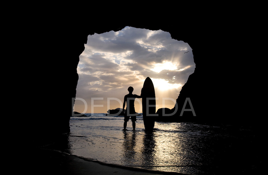 A male surfer stands inside a cave at sunset at Muriwai Beach on the west coast of the North Island, near West Auckland, in New Zealand.