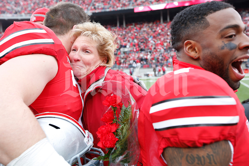 Ohio State Buckeyes offensive linesman Corey Linsley (71) embraces a family member during Senior Day celebration before the college football game between the Ohio State Buckeyes and the Indiana Hoosiers at Ohio Stadium in Columbus, Saturday afternoon, November 23, 2013. The Ohio State Buckeyes defeated the Indiana Hoosiers 42 - 14. (The Columbus Dispatch / Eamon Queeney)