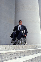 Handicapped man looks at stairs.