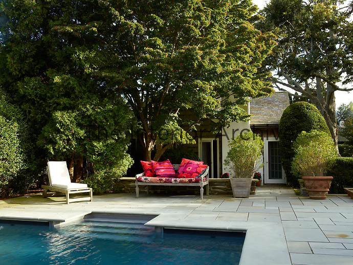Seating is arranged on the paved terrace area beside the pool with shade provided by the established trees.