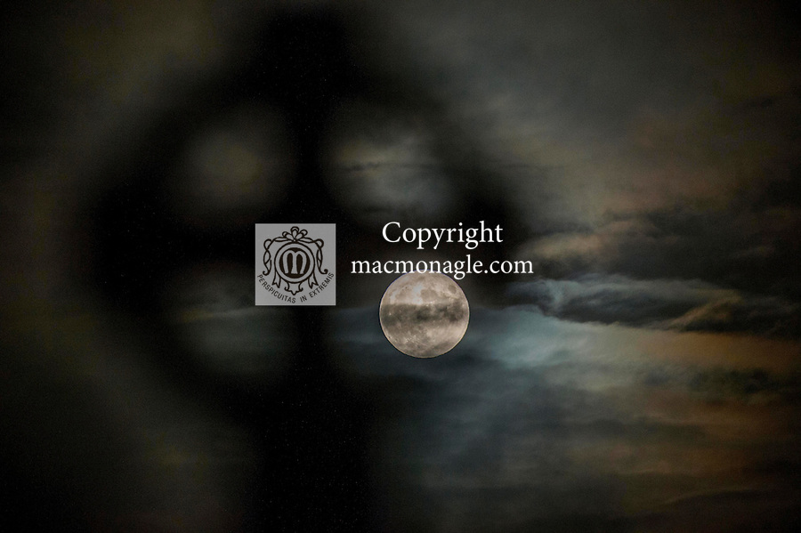 The supermoon seen through the eye of a Celtic Cross in Aghadoe Cemetary, Killarney as it makes a momentary appearance through the clouds around teatime.<br /> Photo Don MacMonagle