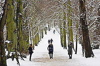 People walk across snow-covered Hampstead Heath, London, United Kingdom