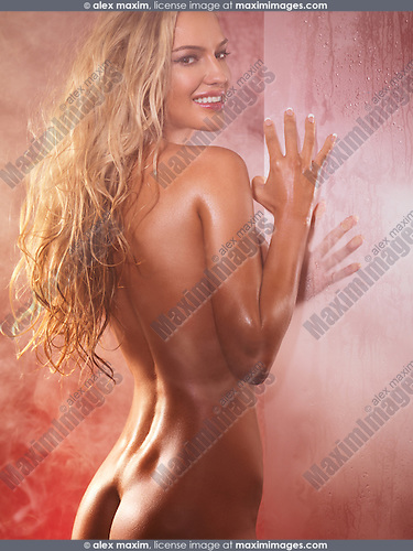 Sexy smiling beautiful woman with nude shiny body and long blond hair in a bath room surrounded with steam