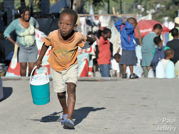 A young survivor of the devastating January 12 earthquake carries water to his family's makeshift shelter in a camp for the homeless in Port-au-Prince, Haiti.