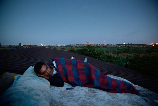 Serbia, Subotica, 11.07.2012: Sajad from Pakistan (name changed) is sleeping on a rooftop. He tried to cross the border to Hungary but got deported back to Serbia several times. In total he already spent 12 months in the Jungle.  <br />