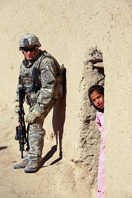 A girl in the village of Pir Zadeh in Maiwand district, Kandahar province, Afghanistan, peers out of her doorway as Staff Sgt. Joshua Rath, 22, of Decatur, Ala. looks on. Rath, a soldier with Company C, 2nd Battalion, 2nd Infantry Regiment, and another soldier were killed four days later when a Taliban suicide bomber blew himself up near their foot patrol in the Maiwand bazaar. Jan. 4, 2009. DREW BROWN/STARS AND STRIPES