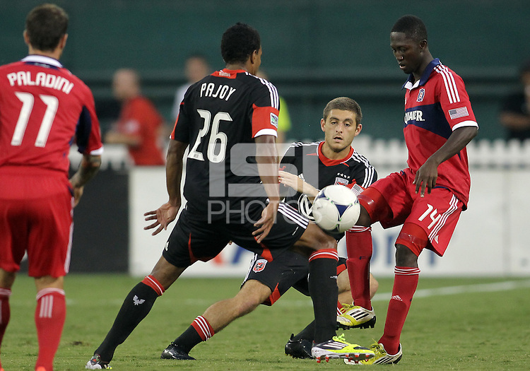 WASHINGTON, DC. - AUGUST 22, 2012:  Lionard Pajoy (26)  and Chris Kolb (22) of DC United stop  Patrick Nyarko (14) of the Chicago Fire during an MLS match at RFK Stadium, in Washington DC,  on August 22. United won 4-2.