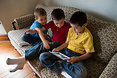 MR / Schenectady, New York. Young children (boys, brothers, 4,7,9) argue about using iPad to read eBook / app at home. ID: AM-Gar. ©Ellen B. Senisi