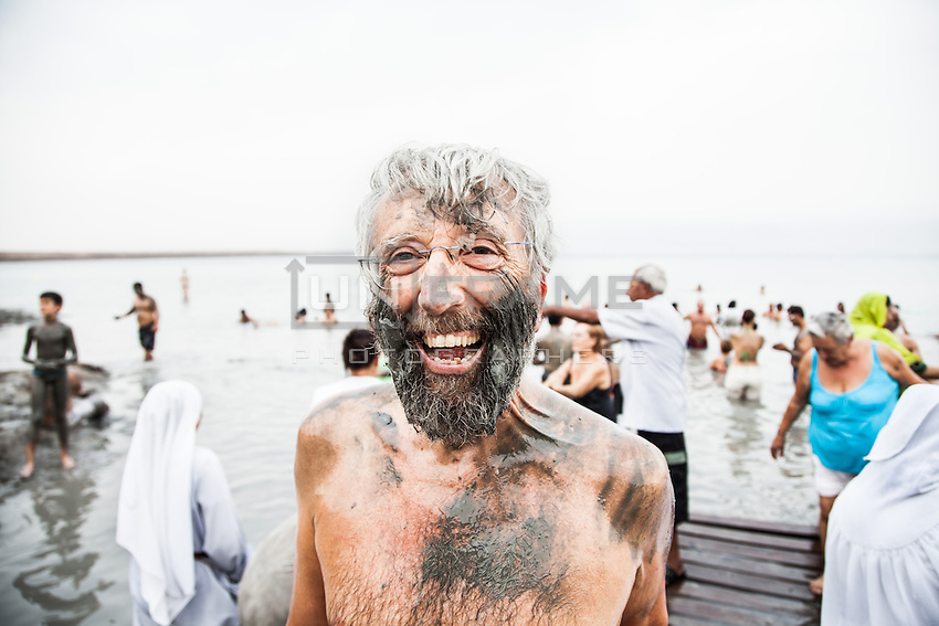 A bather covered in mud following a dip in the Dead Sea, the waters of which are renowned for its health benefits.