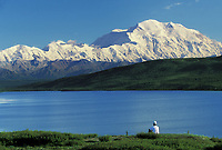 Hiker Sits On The Tundra By Wonder Lake And Takes In The View Of 20, 3020+ Ft. Mt. Denali, Denali National Park, Alaska