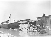 Cleaning up derailment in Espanola of mixed train.  There are four cars on their sides with a load of sacks coming out of a boxcar roof.<br /> D&amp;RG  Espanola, NM  1921