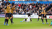 Bafetimbi Gomis of Swansea (C) sits dejected on the ground after denied a goal by Arsenal players during the Barclays Premier League match between Swansea City and Arsenal at the Liberty Stadium, Swansea on October 31st 2015