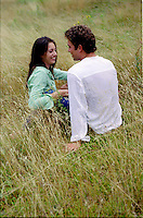 Couple sitting & relaxing in grass