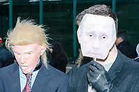 A man wearing a Donald Trump halloween mask stands next to a man holding a cutout of Russian President Vladimir Putin's face after the inauguration of President Donald Trump on Jan. 20, 2017, in Washington, D.C.