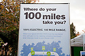 Poster asks 'Where do your 100 miles take you?'. Nissan Leaf Zero Emission Tour promotional event for the Nissan Leaf electric car that is scheduled to be released in Fall 2010. Car specs from Nissan: 5 person capacity, 90 MPH top speed, lithium-ion battery, 100 mile average range per charge. Santana Row, San Jose, California, USA, 12/5/09