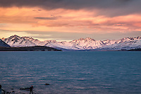 Spectacular sunset colours over Lake Tekapo and the Sib Range.  South Canterbury New Zealand. Photographer in shot.