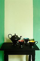A black teapot and collection of cups on a black wooden side table against a green and white painted wall