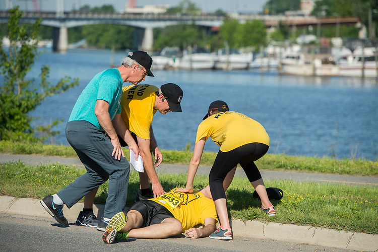 UNITED STATES - MAY 17: A runner is tended to by Dirk Kempthorne, left, ACLI president, and others during the ACLI Capital Challenge 3 Mile Team Race in Anacostia Park, May 17, 2017. The runner was later flown out via helicopter. (Photo By Tom Williams/CQ Roll Call)