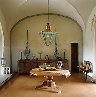 In the grand entrance hall of a Tuscan farmhouse the warm tones of the ochre coloured stone floor and wooden furniture are offset by the grey painted walls