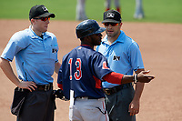 Lowell Spinners manager Corey Wimberly (13) talks with umpires Dylan Bradley (left) and Thomas Fornarola (right) after coach Nate Spears (not shown) was ejected during a game against the Batavia Muckdogs on July 15, 2018 at Dwyer Stadium in Batavia, New York.  Lowell defeated Batavia 6-2.  (Mike Janes/Four Seam Images)