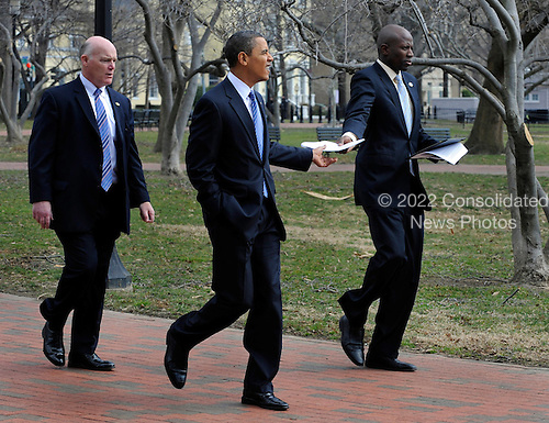 United States President Barack Obama, center, receives a paper from aide Reggie Love as a Secret Service agent trails him, as they walk through Lafayette Park back to the White House after Obama delivered an address at an America's Promise Alliance education event, Monday, March 1, 2010, in Washington,D.C.  Obama announced new steps to improve the nation's schools and improving the lives of America's children and youth.   .Credit: Mike Theiler / Pool via CNP