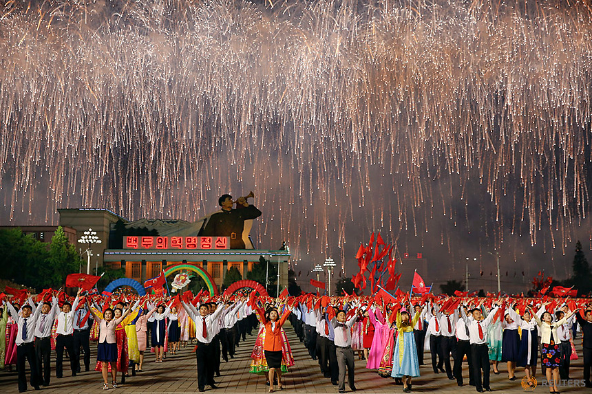 Fireworks explode over participants in a mass dance in the capital's main ceremonial square, a day after the ruling Workers' Party of Korea party wrapped up its first congress in 36 years, in Pyongyang, North Korea May 10, 2016.  REUTERS/Damir Sagolj