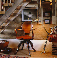 An antique mahogany desk chair and a brass standard lamp beneath the rustic steps to the gallery bedroom