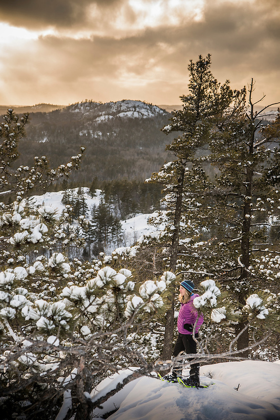 A snow shoe hiker at a scenic overlook during winter from Sugarloaf Mountain in Marquette, Michigan Upper Peninsula of Michigan.