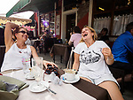 Nevena and Joana have coffee and a laugh at a street cafe, The colorful village of Burano, Italy.