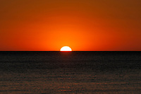 An orange sun sets in a bright orange sky over the ocean near Adelaide, South Australia.