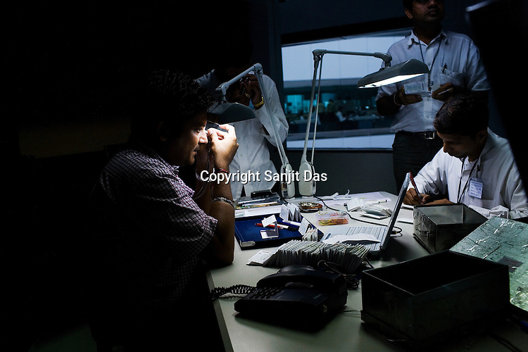 Kamal Shah (left), a diamond specialist checks the shapes of the rough diamonds in the planning section at the diamond cutting and polishing factory in Surat, Gujarat, Western India.